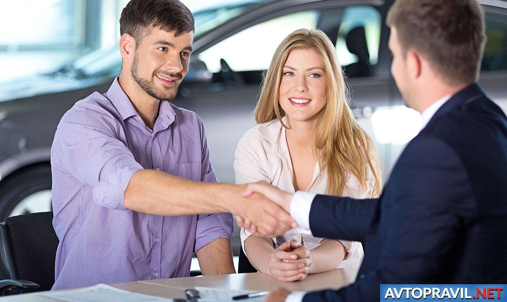 Пара, оформляющая полис ОСАГО в автосалоне