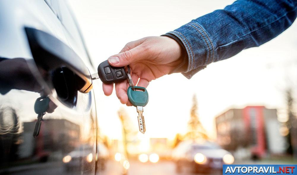 Женщина, открывающая автомобиль ключем