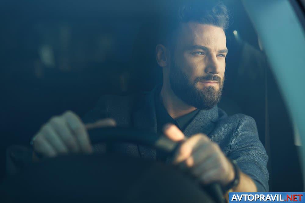 Бородатый мужчина, сидящий за рулем автомобиля