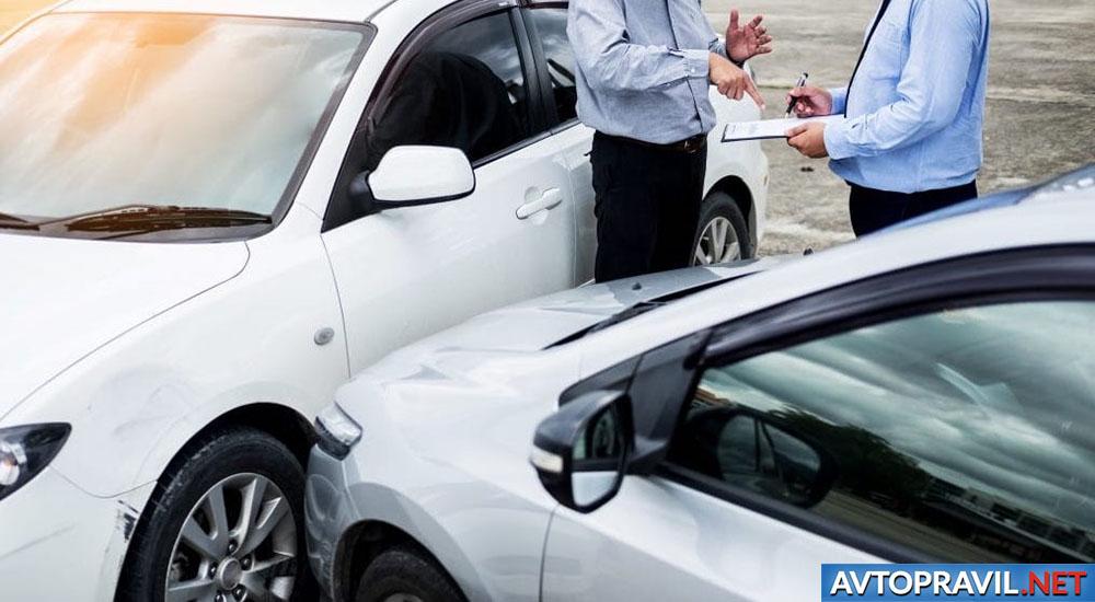 Двое мужчин, разговаривающих возле автомобилей