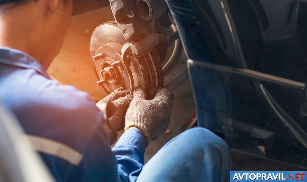 Автомеханик, ремонтирующий автомобиль