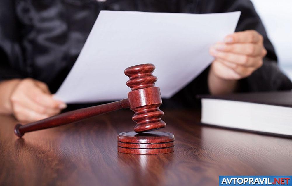 Судья с документами в руках и судейский молоток, лежащий на столе