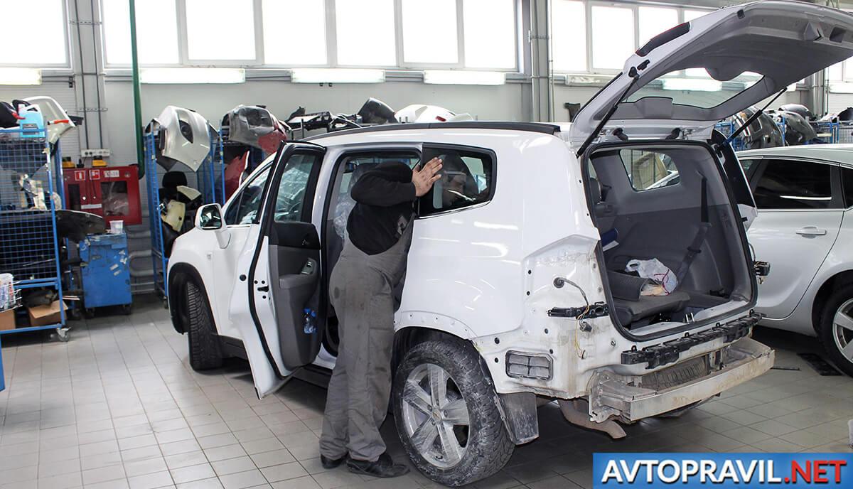Работник СТО, осматривающий салон автомобиля