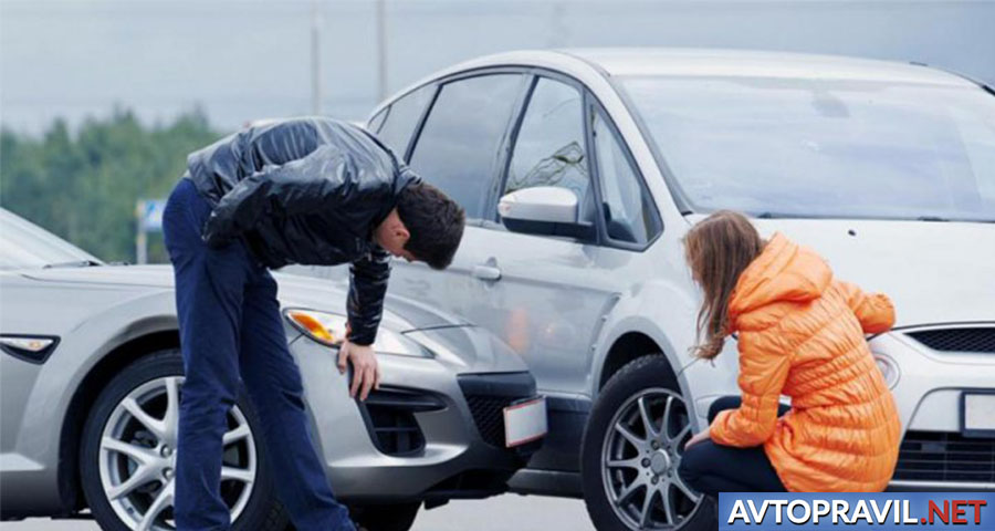 Мужчина и женщина, находящиеся рядом с двумя автомобилями