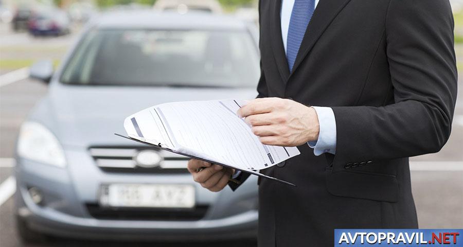 Мужчина, изучающий документы рядом с автомобилем