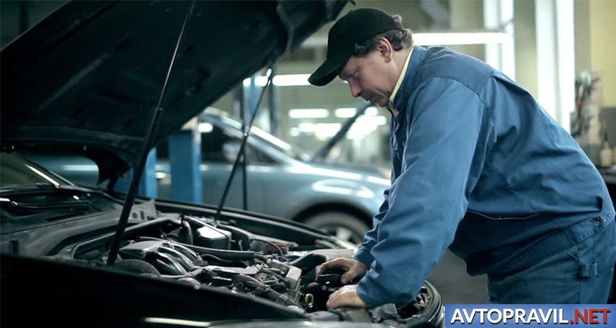 Мужчина, заглядывающий под капот автомобиля