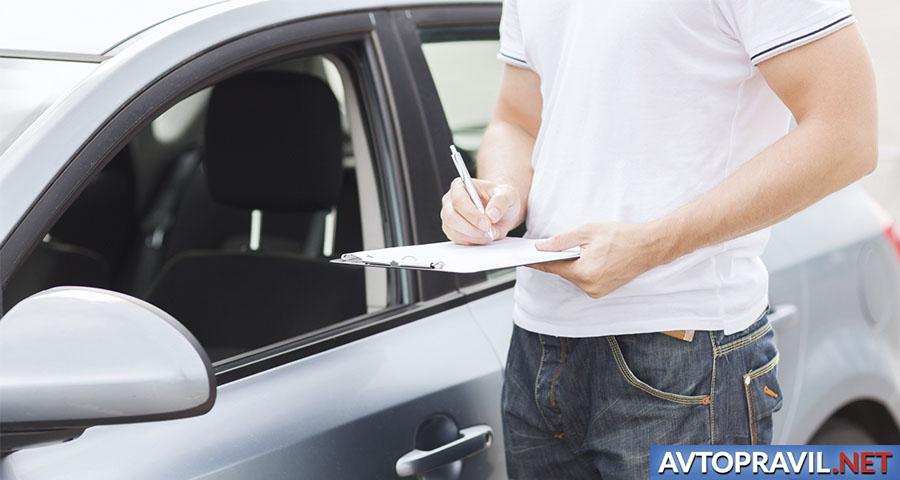 Мужчина, заполняющий документ рядом с автомобилем