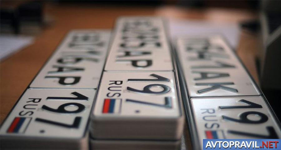 Три стопки автомобильных номеров на столе