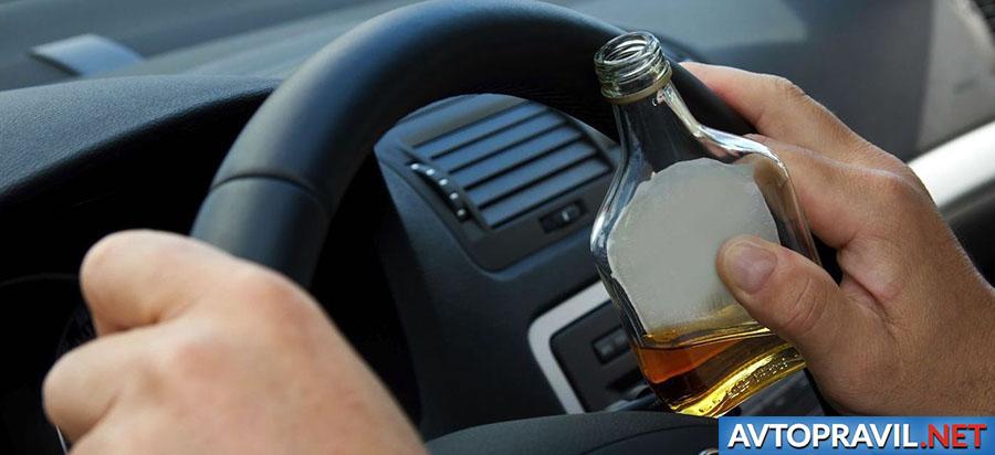 Водитель за рулем с бутылкой в руках