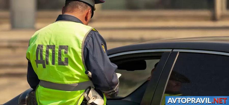 Инспектор, стоящий возле остановленной машины