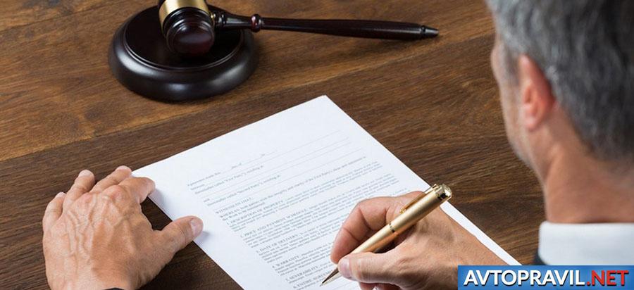 Судья, сидящий за столом с ручкой в руках