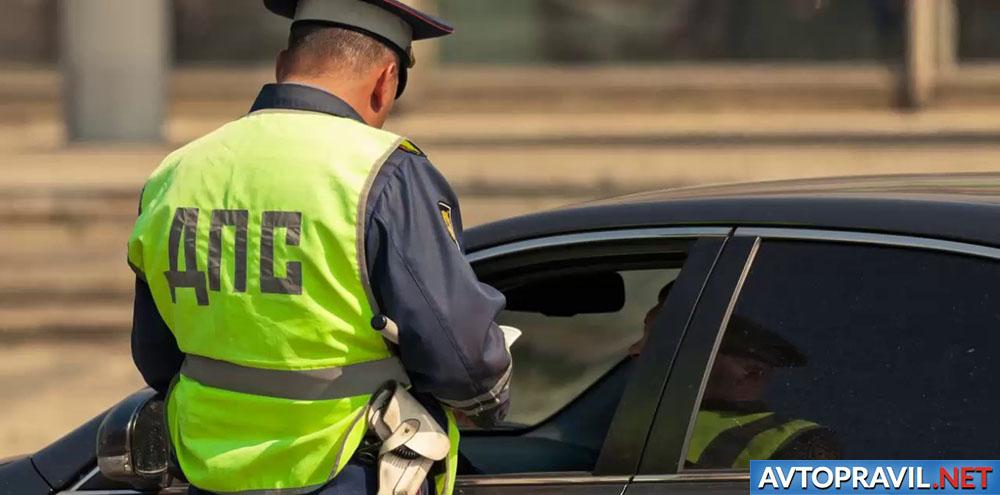 Инспектор ГИБДД, стоящий возле автомобиля