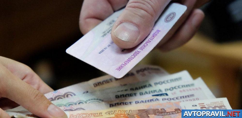 Рубли и водительское удостоверение в руках