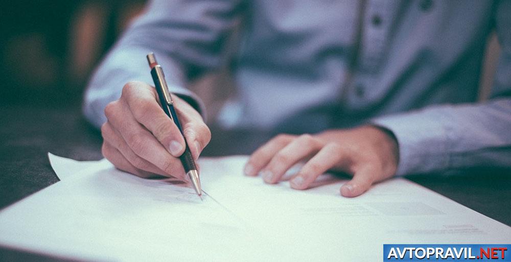 Мужчина, пищущий ручкой на листе бумаги