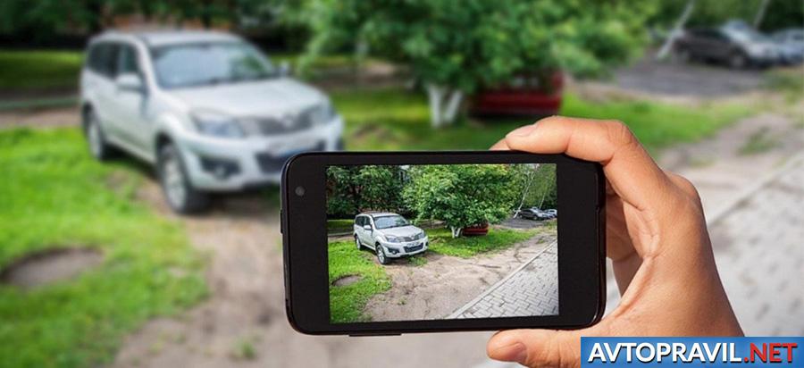 Экран телефона с фотографией автомобиля на газоне