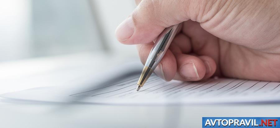 Рука с ручкой, заполняющая документы