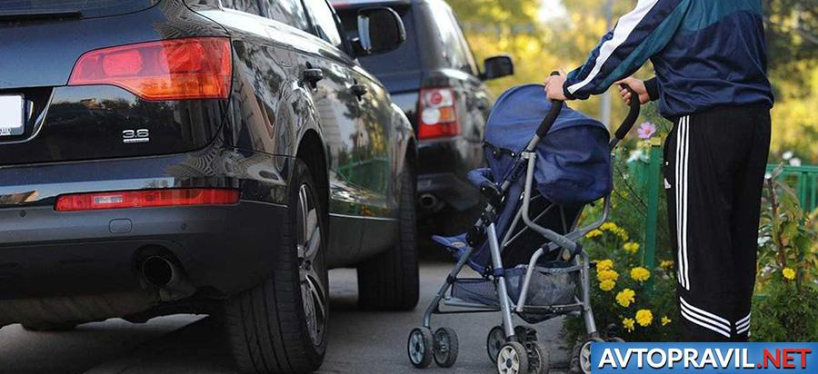 Автомобиль, стоящий на тротуаре и мужчина с коляской