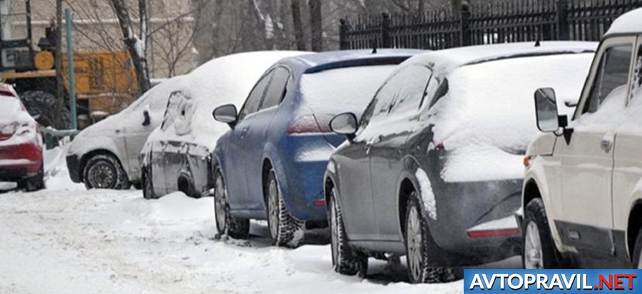 Машины, стоящие на газоне на снегу